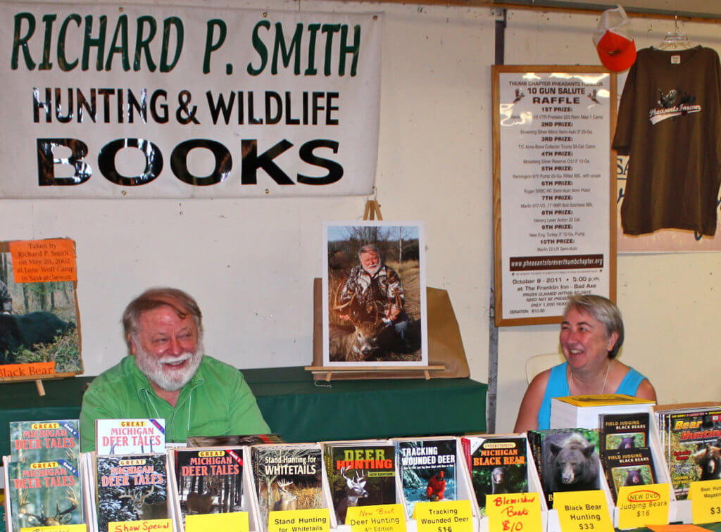 Richard P. Smith and wife Lucy LaFaive in their booth selling Richard's whitetail deer, black bear, hunting and wildlife books and DVDs at Woods-N-Water Outdoor Weekend in Imlay City, MI